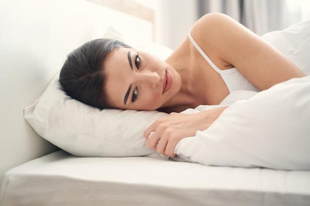 Portret smutnej, zamyślonej, pięknej młodej kobiety rasy kaukaskiej leżącej na poduszce w łóżku