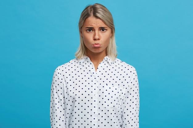 Portret smutnej zdenerwowanej blond młodej kobiety nosi koszulkę w kropki, czuje się przygnębiona i odizolowana na niebieskiej ścianie