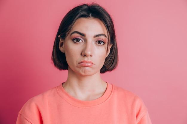 Portret smutnej zdenerwowanej młodej kobiety z jasnym makijażem na różowym tle