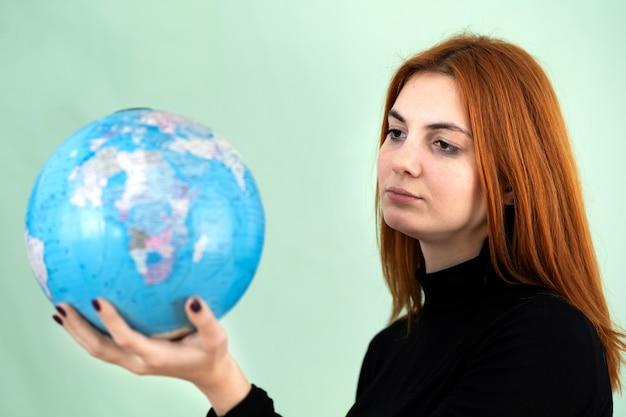 Portret smutnej zmartwionej młodej kobiety trzymającej geograficzny świat świata w dłoniach. cel podróży i koncepcja ochrony planety.
