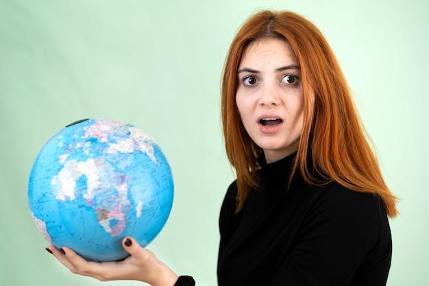 Portret smutnej zmartwionej młodej kobiety trzymającej geograficzny świat świata w dłoniach.