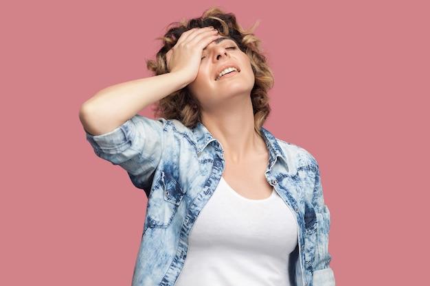 Portret smutnej zmartwionej młodej kobiety z kręconymi fryzurami w dorywczo niebieskiej koszuli stojącej, trzymającej rękę na czole i smutnej, ponieważ straciłem wszystko. kryty strzał studio, na białym tle na różowym tle.