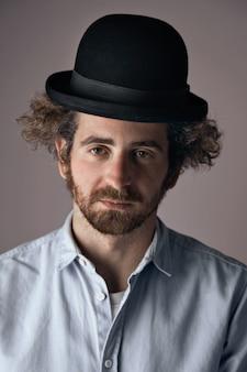 Portret smutno wyglądający młody, brodaty żyd z kręconymi włosami, ubrany w śmieszny czarny melonik i jasną dżinsową koszulkę z guzikami na białym tle na jasnoszarym tle.