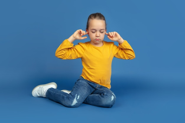 Portret smutny dziewczynka siedzi na białym tle na niebieskim tle studio. jak to jest być autystą. współczesne problemy, nowa wizja spraw społecznych. pojęcie autyzmu, dzieciństwa, opieki zdrowotnej, medycyny.
