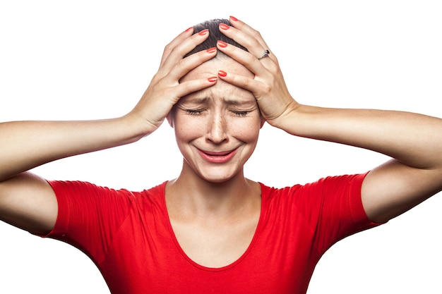 Portret smutny nieszczęśliwy płacz kobiety w czerwonej koszulce z piegami. zamknięte oczy ręce na głowie, studio strzał. na białym tle.