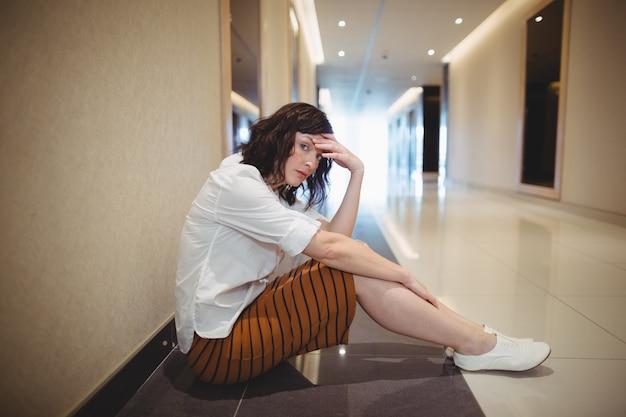 Portret smutny żeński wykonawczy siedzi na korytarzu