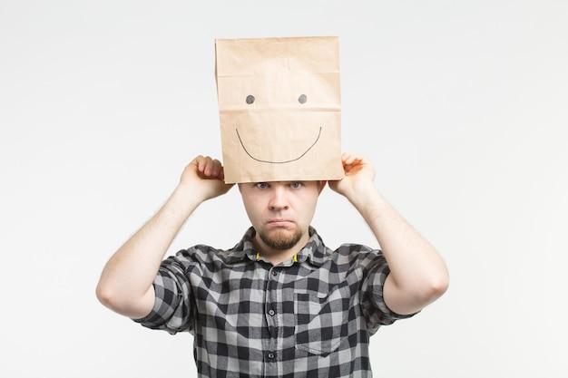 Portret smutnych mężczyzn zdejmujących szczęśliwą papierową maskę w