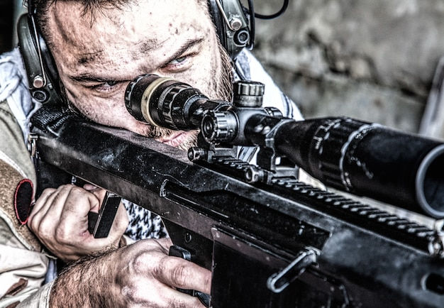 Portret snajpera us navy seal na stanowisku strzeleckim, uzbrojonego w karabin snajperski dużego kalibru z celownikiem teleskopowym, noszącego taktyczne słuchawki z mikrofonem, obserwującego terytorium, przeszukującego cele