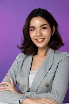 Portret snap rysunek, biznes kobieta stoisko w szarym garniturze, studio oświetlenie gradientowe fioletowe tło, azjatyckie 20s modelka z twarz oczy ręce ramię szczęśliwy uśmiech wygląda atrakcyjnie