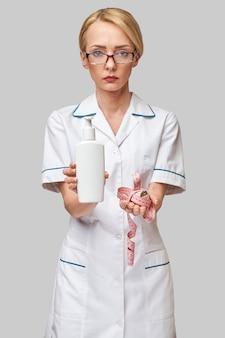 Portret specjalisty od urody, trzymając w ręku butelkę balsamu do ciała i miarkę.