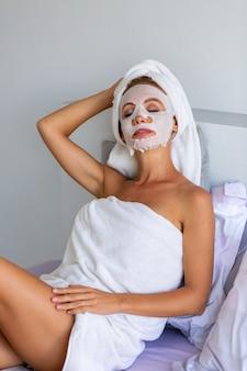 Portret spokojnej kaukaski ładnej kobiety z ręcznikiem na głowie i masce