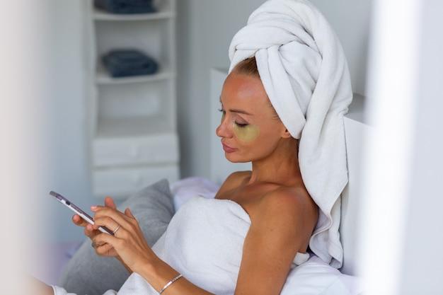 Portret spokojnej kaukaskiej ładnej kobiety z ręcznikiem na głowie i maską na oczy z łatami na twarzy koncepcja pielęgnacji skóry twarzy kobieta relaksuje się w łóżku w domu weź selfie zegarek telefon