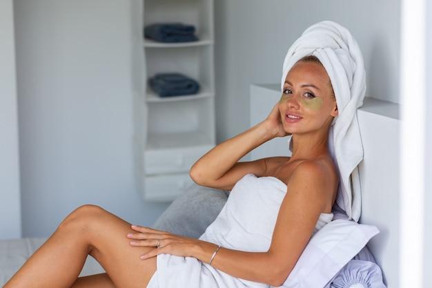Portret spokojnej kaukaskiej ładnej kobiety z ręcznikiem na głowie i maską na oczy z łatami na twarzy koncepcja pielęgnacji skóry twarzy kobieta relaksuje się w łóżku w domu
