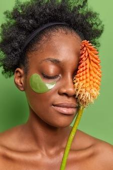 Portret spokojnej kobiety wykonuje w domu zabiegi przeciwzmarszczkowe, używa nowoczesnych kosmetyków, kosmetyków wykonanych z naturalnych składników, nosi hydrożelowe plastry pod oczami, stoi bez koszuli.