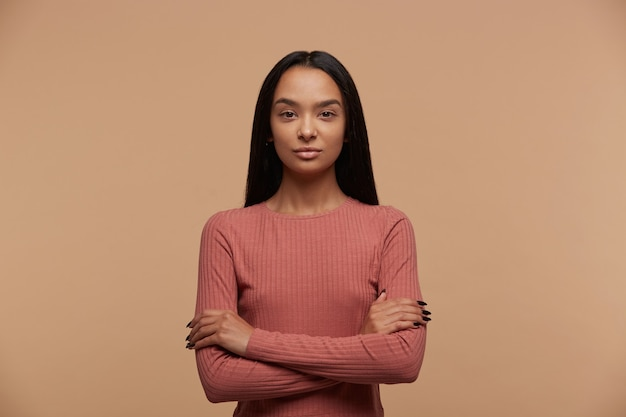 Portret spokojnej, pewnej siebie, atrakcyjnej młodej kobiety brunetka stoi z rękami skrzyżowanymi