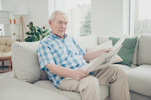 Portret spokojny dziadek siedzi na tapczanie, czytając gazetę
