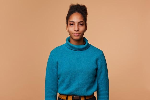 Portret spokojny młody african american kobieta z kręconymi ciemnymi włosami, ubrany w niebieski sweter, na białym tle.