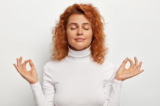 Portret spokojny, zrelaksowany, piękna modelka praktykuje jogę medytuje z zamkniętymi oczami