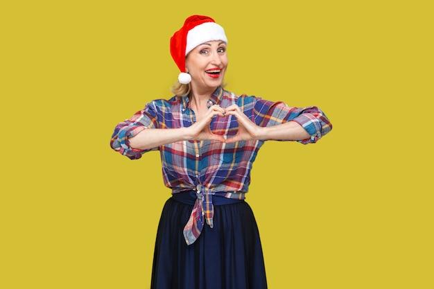 Portret spokoju atrakcyjna kobieta w czerwonej czapce santa i kraciastej koszuli stojącej i czyniąc serce palcami i uśmiechnięty ząb, patrząc na kamery. wewnątrz, strzał studyjny, żółte tło