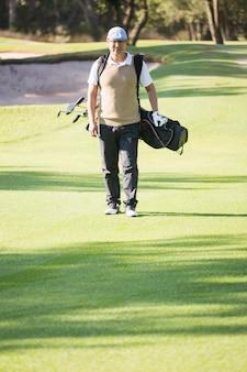 Portret sportowca spaceru z jego torbę golfową