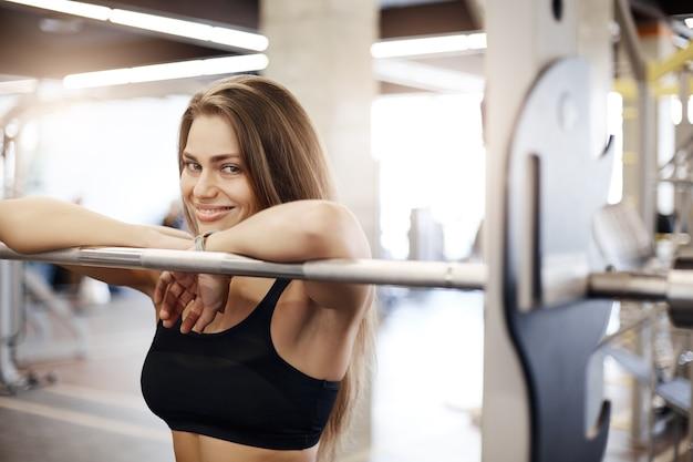 Portret sportowca szczęśliwa młoda dama opierając się na poprzeczce lub dzwonku, uśmiechając się w jasnym otoczeniu siłowni.