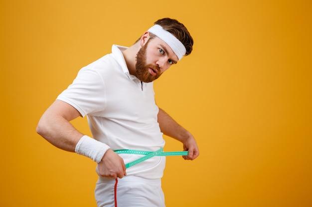 Portret sportowego mężczyzna mierzy jego talię z taśmą