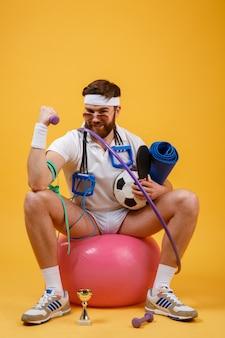 Portret sportowego mężczyzna obsiadanie na sprawności fizycznej piłce