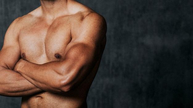 Portret sportowego, muskularnego mężczyzny topless ze skrzyżowanymi rękami