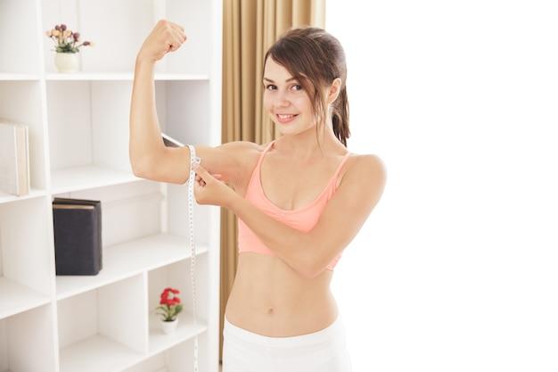Portret sportowej kobiety uśmiechnięta, podczas gdy mierzy jej bicepsy miarką