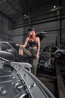 Portret sportowej kobiety w dżinsach i top stoi z zdemontowanym samochodem w garażu.