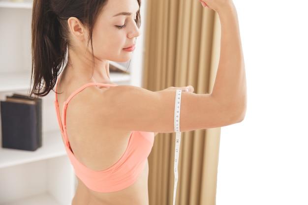 Portret sportowej kobiety z bliska mierzy bicepsy miarką