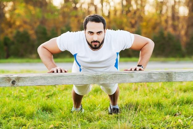 Portret sportowy mężczyzna 30s w odzieży sportowej robi pompki w zielonym parku.