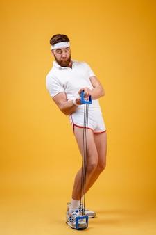 Portret sportowy mężczyzna ćwiczy z gumowym ekspanderem