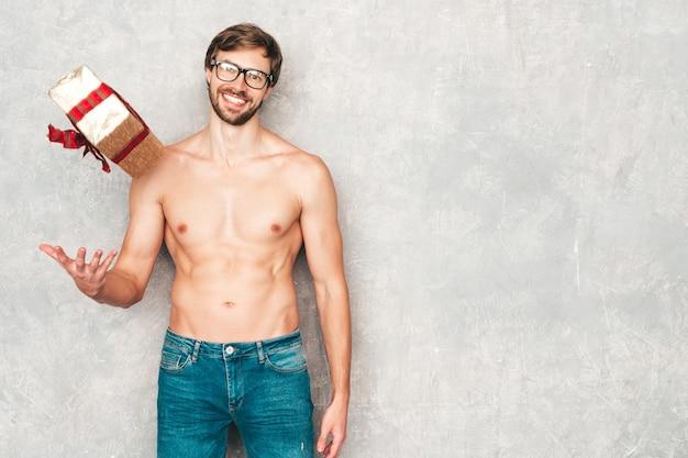 Portret sportowy przystojny silny mężczyzna. model zdrowego fitness lekkoatletycznego pozowanie w pobliżu szarej ściany w dżinsach.