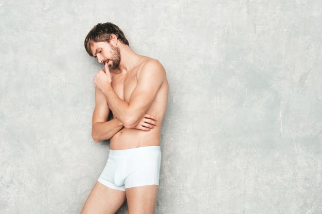 Portret sportowy przystojny silny mężczyzna. zdrowy uśmiechający się model fitness lekkoatletycznego pozowanie w pobliżu szarej ściany w białej bieliźnie.