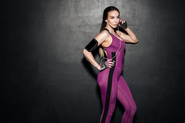 Portret sportowy seksowną kobietą słuchania muzyki w słuchawkach