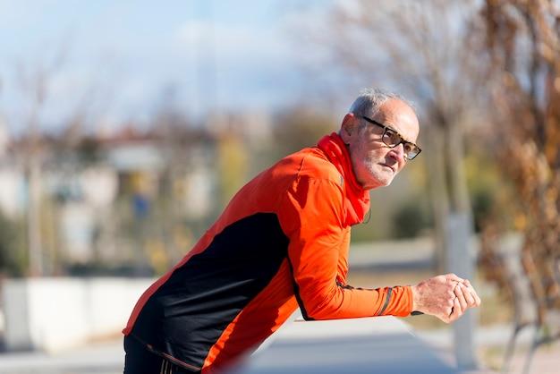 Portret sportowy starszy mężczyzna opiera na ogrodzeniu