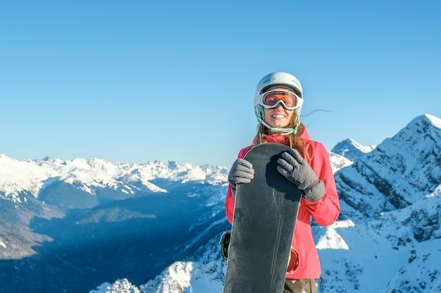 Portret sportsmenka jest ubranym hełm i maskę z snowboard w ręce patrzeje kamerę