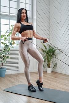 Portret sportsmenki w średnim wieku, która dba o swoje ciało i zdrowie, wykonując ćwiczenia fizyczne na siłowni.