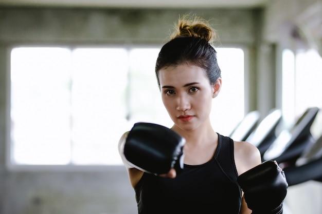 Portret sporty dziewczyny piękna kobieta z tylnymi bokserskimi rękawiczkami trenuje przy gym