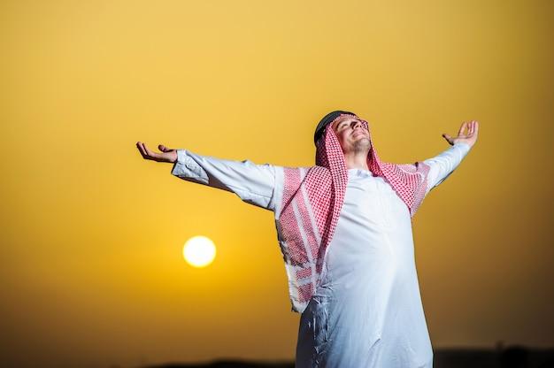 Portret spragnionego arabskiego mężczyzny na środku żółtej pustyni.