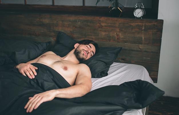 Portret sprawnego męskiego modelu śpiącego w luksusowej sypialni skąpanej w jasnym świetle porannego okna