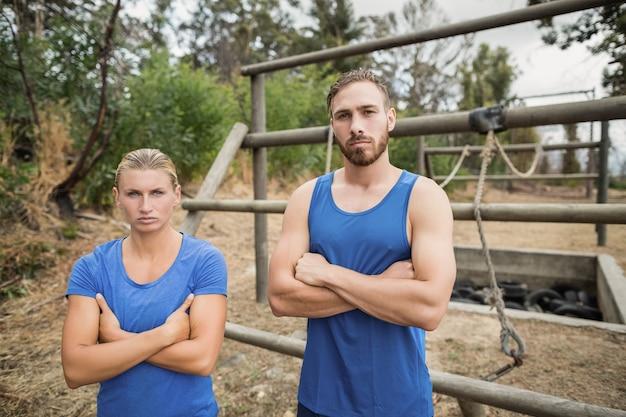 Portret sprawnego mężczyzny i kobiety stojącej z rękami skrzyżowanymi podczas szkolenia boot camp
