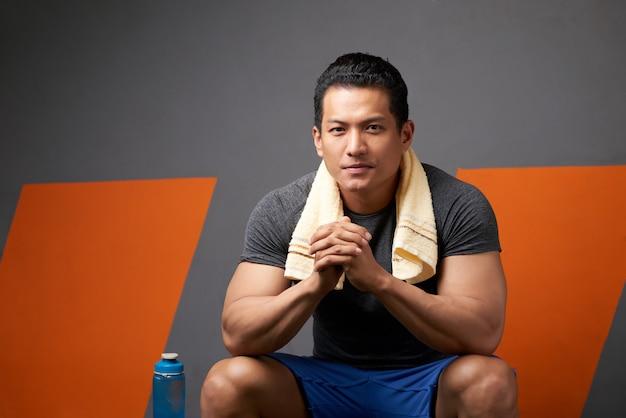 Portret sprawny człowiek z palcami splecione, siedząc na kanapie siłowni po treningu