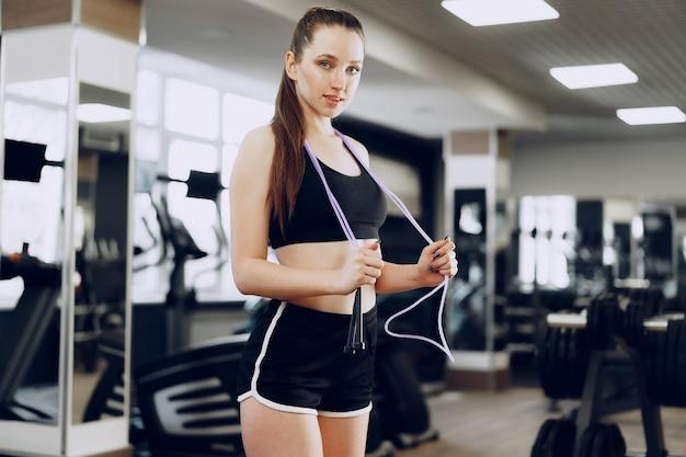 Portret sprawny dziewczyna z skakanka stojąc w siłowni