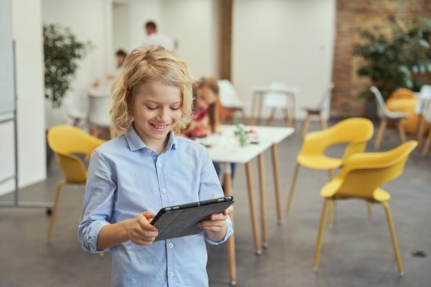 Portret sprytnego małego chłopca uśmiechającego się przy użyciu komputera typu tablet podczas pozowania do kamery podczas zajęć macierzystych