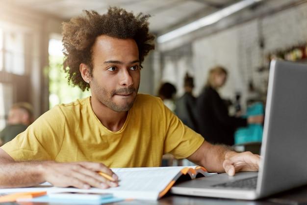 Portret sprytnego studenta o ciemnej skórze i krzaczastych włosach, ubrany w zwykłe ubrania, siedzący w kafeterii, pracujący przy swoim kursie, szukający informacji w internecie za pomocą laptopa