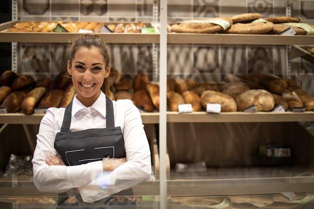 Portret sprzedawcy piekarni z założonymi rękami stojącego przed półką pełną wyhodowanych bułeczek i ciasta