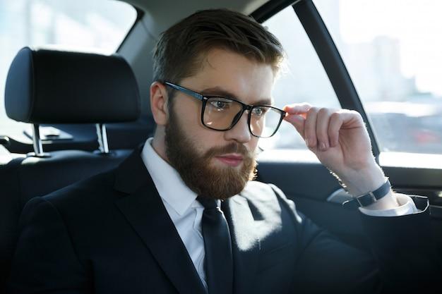 Portret srious młody człowiek ubrany w garnitur i okulary