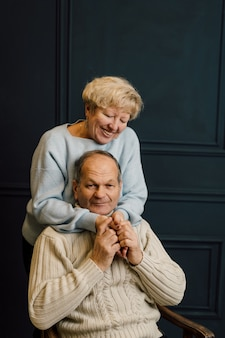 Portret stara para żona i mąż przytulanie i uśmiechnięte. ciemnoniebieskie tło. szczęśliwi kochankowie na emeryturze. stop ageizmowi. . wysokiej jakości zdjęcie